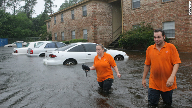 Lillian Murphy and co-worker Joseph Stanley wade through floodwaters Sunday at her Pensacola apartment complex.