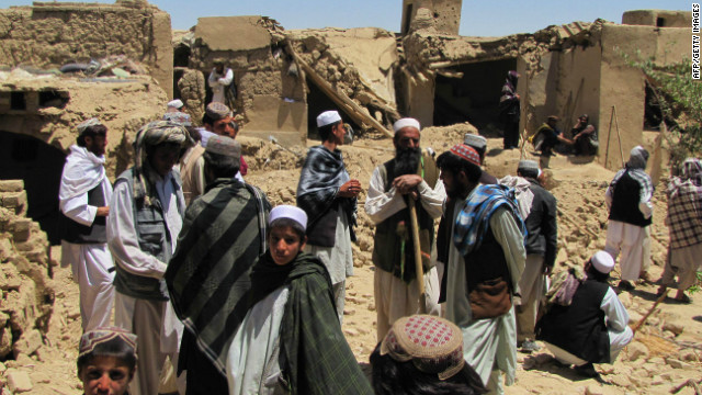 Afghan villagers stand outside a house which was hit by a NATO airstrike in Sajawand village, south of Kabul on June 6, 2012.