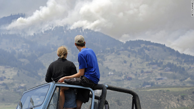 Michelle Mellenthin and Chris Huizenga watch firefighting efforts Monday from a Jeep near Laporte.