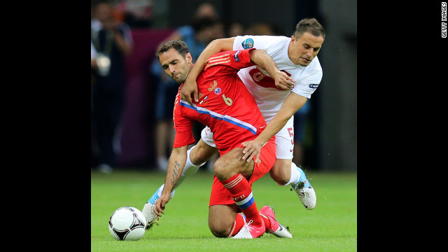 Roman Shirokov of Russia and Dariusz Dudka of Poland vie for control of the ball during their match, Tuesday.