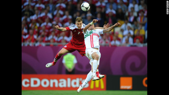 Nicklas Bendtner of Denmark beats Pepe of Portugal to head in Denmark's second goal.