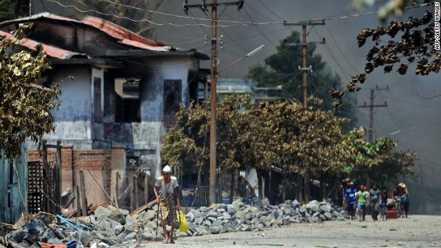 Evacuated Muslims walk past burnt houses in Sittwe, capital of Myanmar's western state of Rakhine, on Tuesday.