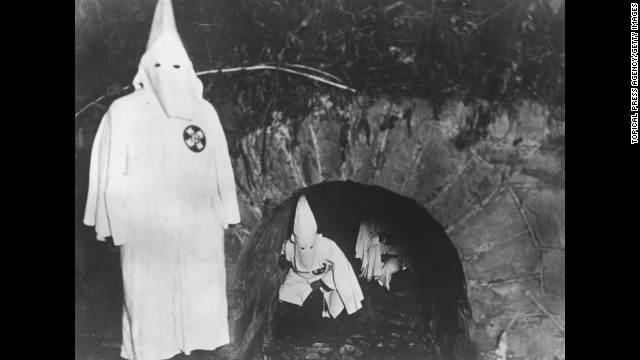 Ku Klux Klan members crawl out of a tunnel after a meeting in 1922.