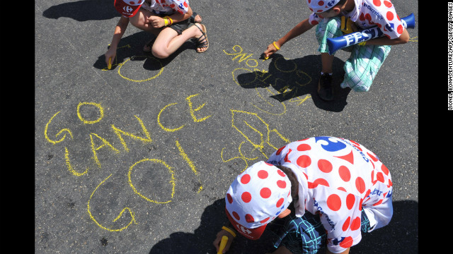 Young Armstrong fans write messages on the ground ahead of the 2009 Tour de France. He came in third place that year.