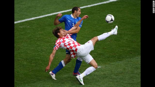Giorgio Chiellini of Italy and Nikica Jelavic of Croatia compete for the ball.