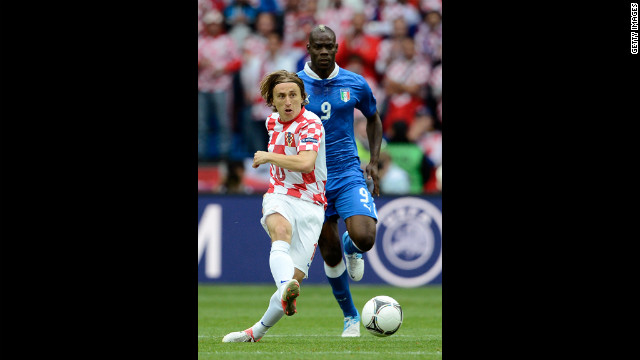 Luka Modric of Croatia is marshalled by Mario Balotelli of Italy.