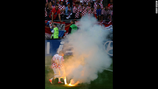 Ognjen Vukojevic and Ivan Perisic of Croatia stand by after a flare was thrown onto the field.
