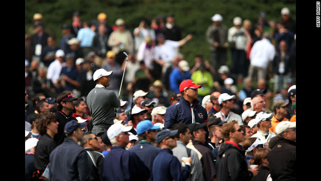 Surrounded by spectators, Woods watches a shot on the 18th tee.