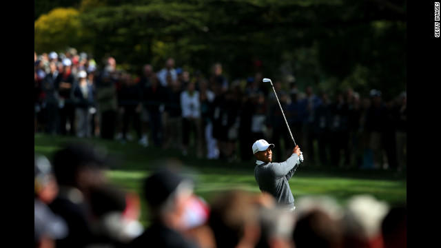 Tiger Woods watches his approach shot on the 18th hole during the first round .