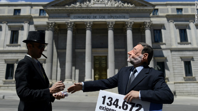 Activists stage a performance depicting Prime Minister Mariano Rajoy and a banker outside the Congress of Deputies in Madrid on June 12, 2012. The demonstration came days after Spain secured a eurozone banking bailout of 100 billion euros ($125 billion).