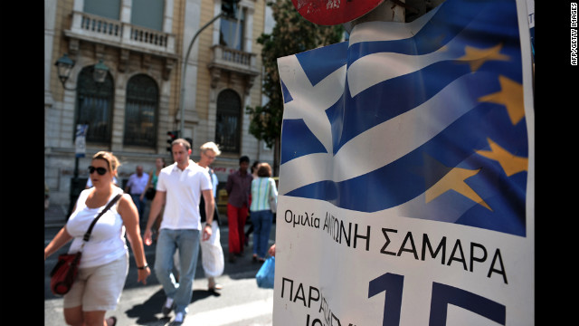 People walk by pre-election posters of the conservative New Democracy Party in Athens on Friday, June 15. Greece votes for the second time on Sunday.