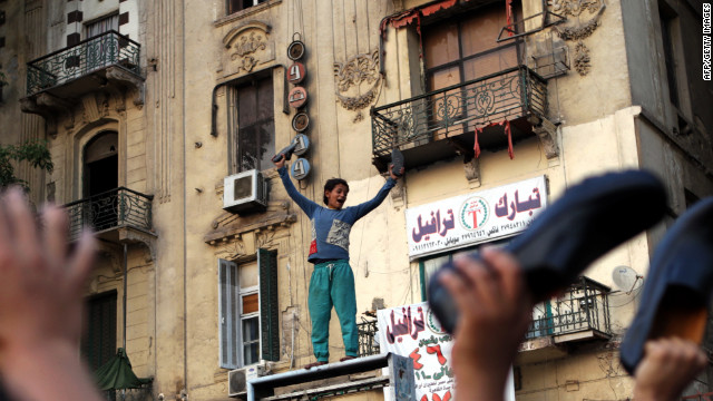 An Egyptian boy waves his shoes as he joins supporters of the Muslim Brotherhood in a protest in Cairo's Tahrir Square against Mubarak-era prime minister and presidential candidate Ahmed Shafiq after Egypt's top court rejected on Thursday a law barring him from standing in a tense presidential poll runoff.