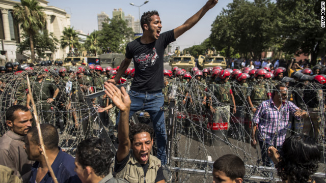 A protestor stands on a barricade of barbed wire as Egyptian military police stand guard. Egypt's Supreme Constitutional Court ruled that the Islamist-led parliament must be immediately dissolved.