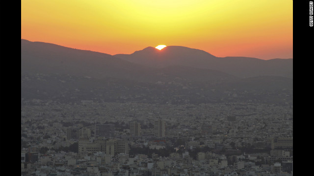 The sun rises over the skyline in Athens.