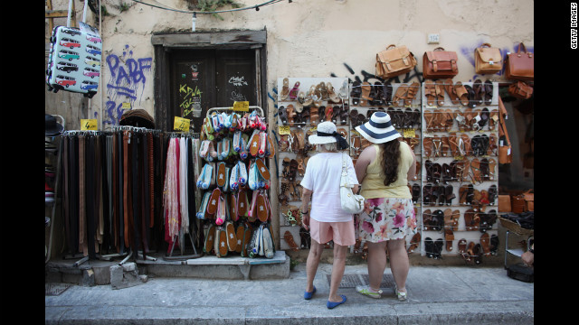 Tourists peruse leather goods for sale in the district of Plaka.