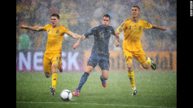 Yevhen Selin of Ukraine and Yevhen Khacheridi put pressure on Jeremy Menez of France during the group D match between Ukraine and France.