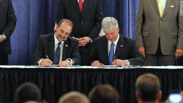 Denis Lebel, Canada's transport minister, and Michigan Gov. Rick Snyder sign an agreement to build the new bridge.