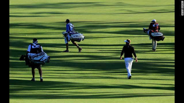 Luke Donald of England walks up a fairway with a group of caddies during the second round.