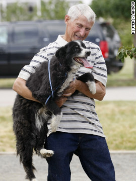 Resident Bill Janz reunites with his dog Abby on Wednesday. Abby had been at Janz's home when the fire started. She jumped into a fire truck as it approached the house, escaping the fire.