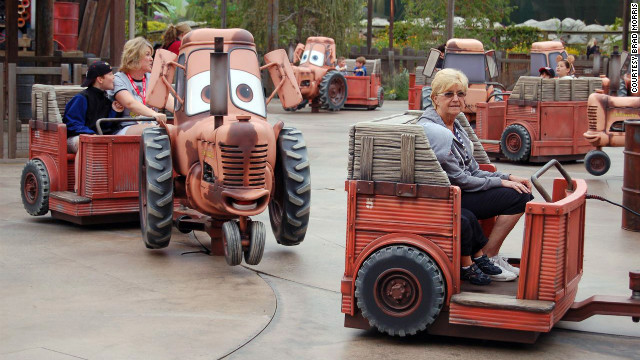 Riders of Mater's Junkyard Jamboree listen to cheerful songs as the tractors carrying them dance. 