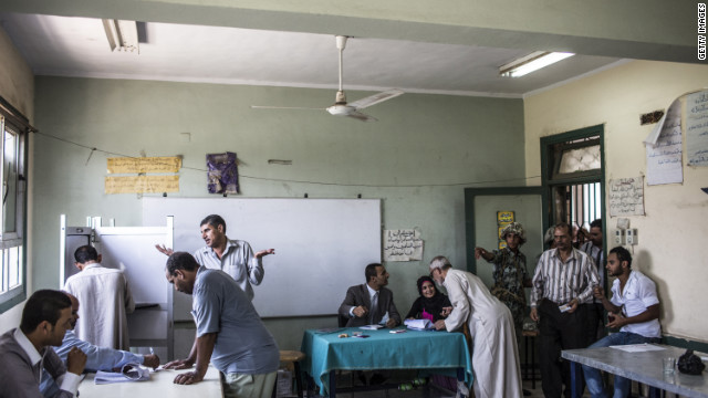 Election officials and an Egyptian soldier direct voters during the second stage of runoff presidential elections at a polling station in Giza.
