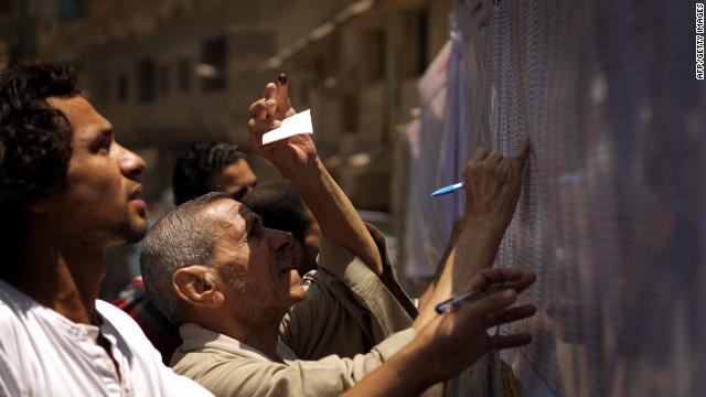 Egyptian Christian Coptic men check the voters' list Saturday outside a polling station in the Cairo Coptic neighborhood of Shubra.
