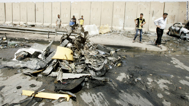 Residents gather at the site of a bomb attack in Baghdad on Saturday. 