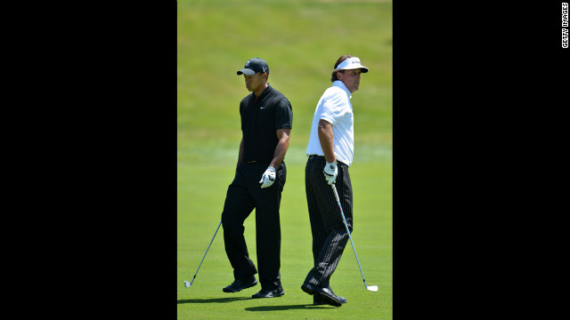 Tiger Woods and Phil Mickelson walk past one another during the second round.