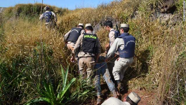 Police on Friday drag the body of one of the peasants shot dead during an eviction of squatters in Curuguaty.