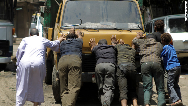Egyptians push a truck that was blocking the entrance of a polling station.