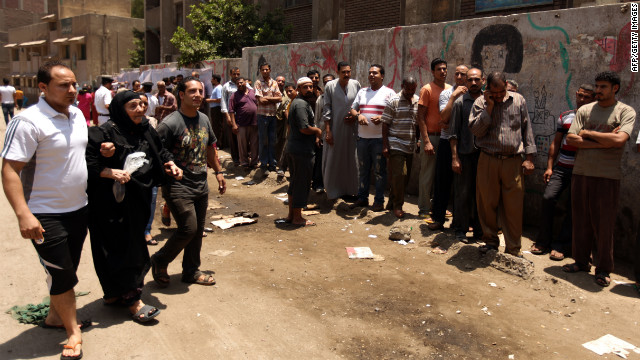 Egyptian Christian Coptic men help a woman reach a polling station in the Cairo Coptic Shubra neighborhood on Saturday, June 16. Voters returned to the polls after Egypt's Supreme Constitutional Court ruled Thursday that the Islamist-led Parliament must be immediately dissolved.
