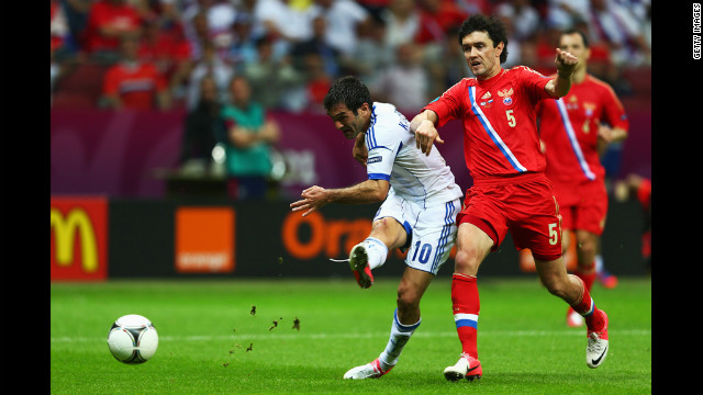 Giorgos Karagounis of Greece scores the opening goal under pressure from Yuriy Zhirkov of Russia during the match between Greece and Russia on Saturday.