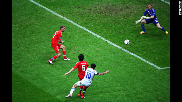 Giorgos Karagounis of Greece scores the opening goal past Vyacheslav Malafeev of Russia during the match between Greece and Russia.