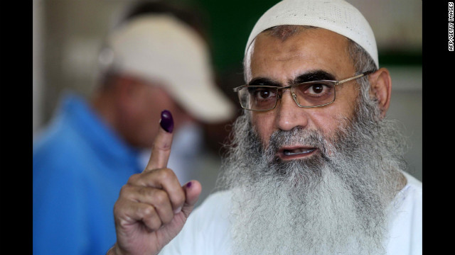 An Egyptian Muslim Salafist shows his ink-stained finger after voting a polling station.