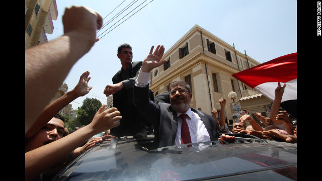 Egyptian Muslim Brotherhood candidate Mohammed Mursi, center, waves to his supporters as he arrives at a polling station to vote in the city of Zagazig.