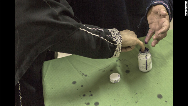 Egyptian women dip their fingers in ink after voting at a polling station.