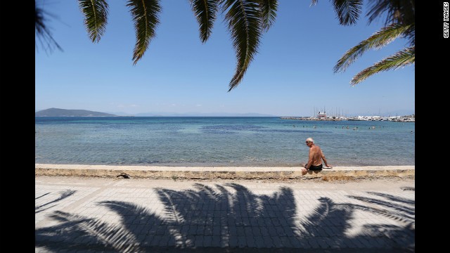 A man relaxes in the sun at a beach on the island of Aegina on June 16 in Aegina, Greece.