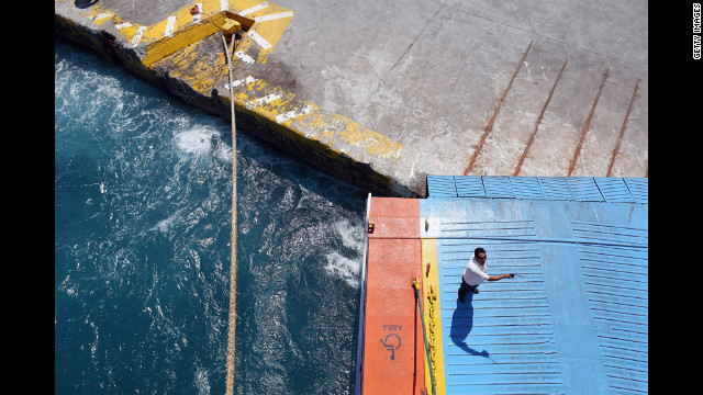 A man directs passengers as they disembark from a ferry at the island of Aegina on June 16.