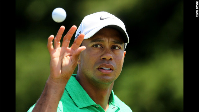 Tiger Woods of the United States reaches for a golf ball on the practice ground.
