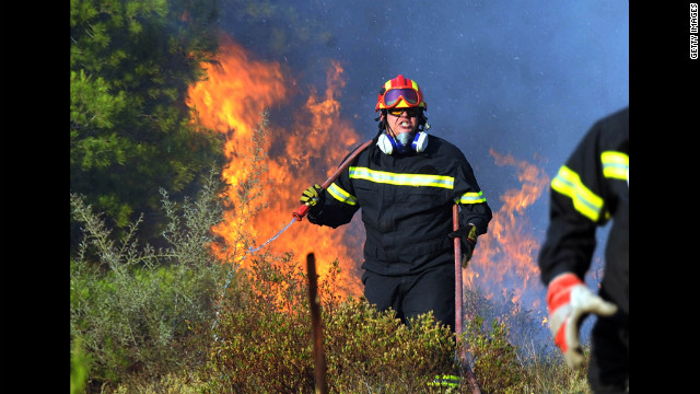 A firefighter works on extinguishing a brush fire in the eastern Athens area of Keratea. Two brush fires broke out in Greece on June 16 including one near seaside resorts close to Athens, just a day ahead of crucial elections, the fire service's media office said. Winds of up to 70 kph (45 mph) were pushing flames to residental areas.