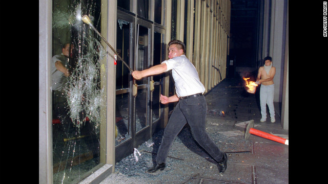 A rioter breaks a glass door of the Criminal Courts building, downtown Los Angeles on April 29.