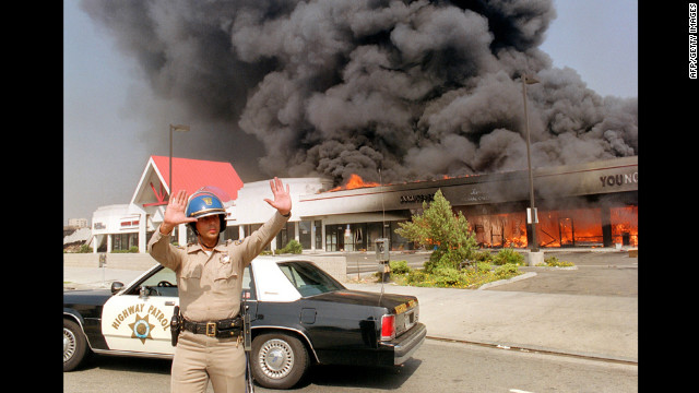 A California Highway patrolman directs traffic around a shopping center engulfed in flames on April 30.