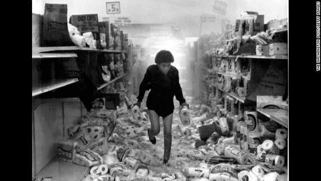 A woman runs out of a store that has been heavily looted as the overhead sprinkler system is triggered on May 1. More than 700 retail stores were damaged during the riots.
