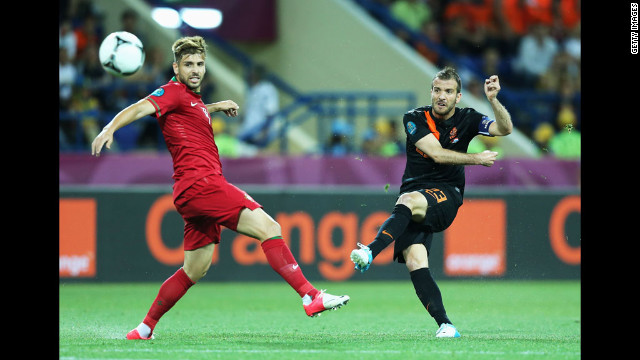 Rafael van der Vaart of the Netherlands scores the opening goal past Miguel Veloso of Portugal.