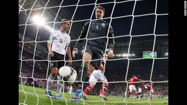Philipp Lahm and Manuel Neuer of Germany walk toward the ball after Michael Krohn-Dehli of Denmark scored.