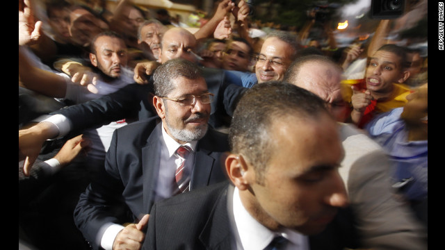 The Muslim Brotherhood's Mohamed Morsi makes his way through supporters at electoral headquarters early Monday in Cairo. In a victory speech, Morsi did not address the military council's move but tried to allay fears he would impose an Islamist state.