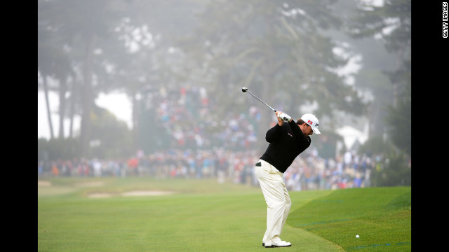 Graeme McDowell hits his second shot on the sixth hole.