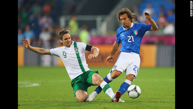 Kevin Doyle of Ireland tackles Andrea Pirlo of Italy.
