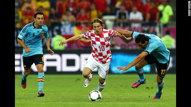 Luka Modric of Croatia is closed down by Alvaro Arbeloa and Xavi of Spain.