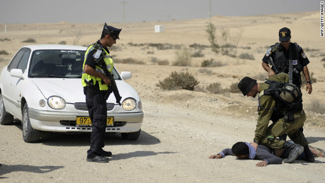 An Israeli soldier detains an Arab Israeli after he tried to pass a police roadblock Monday.